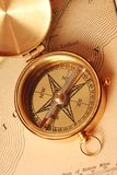 Antique brass compass. Over old map background stock photos