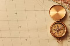Antique brass compass. Over old map background royalty free stock photo