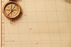 Antique brass compass. Over old map background stock image