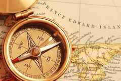 Antique brass compass. Over old Canadian map background royalty free stock photo