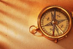 Antique brass compass. Over old map background royalty free stock photos