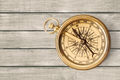 Brass antique compass on wooden background. Antique brass compass background object decorative equipment Royalty Free Stock Images