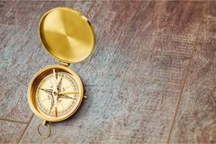 Brass antique compass on wooden background. Antique brass compass background object decorative equipment Stock Image