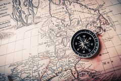 Brass antique compass on old brown map. Antique brass compass background object paper decorative Royalty Free Stock Image