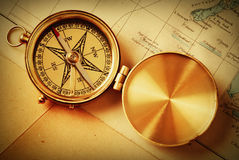 Antique brass compass over map stock photography