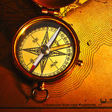 Antique brass compass over old background Royalty Free Stock Images
