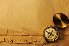 Antique brass compass over old background Stock Photos