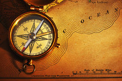 Antique brass compass over old USA map. Background stock photo