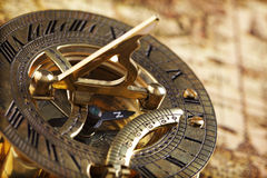 Antique brass compass and sundial. On world map royalty free stock photography
