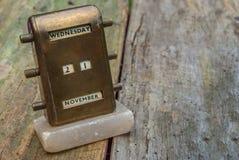 Antique Brass Desktop Perpetual Calendar. On an Old wooden floor stock photo