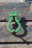 Antique brass door knocker on a wooden door Royalty Free Stock Photos