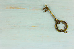 Antique brass key on a pale green distressed wood background. Stock Photos