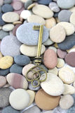 Antique Brass key on a pebble beach Royalty Free Stock Photography