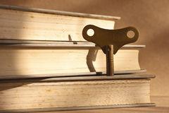 Antique brass winder key. Standing on stack of old books for the key of success concept Royalty Free Stock Photo