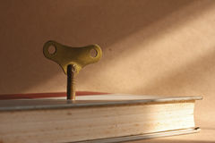 Antique brass winder key. Standing on old book for the key of success concept Stock Photography