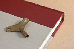 Antique brass winder key. Lying on old book for the key of success concept Stock Photos