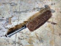 Antique Bristle Dustpan Brush on Worn Linoleum Countertop. A vintage, wood handle brush with hard bristles rests on an old linoleum surface Stock Image