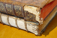 Antique broken books over a yellow background. Literature Stock Photography