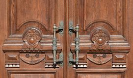 Antique bronze handles on an old wooden door. Wood carving, part of an old building stock images