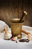 Antique bronze mortar and pestle with spice. (garlic, bell pepper) on white tablecloth around a wooden wall Royalty Free Stock Images