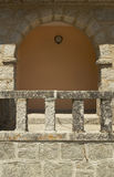 Antique building rock facade with arch and warm tone wall. Royalty Free Stock Photos