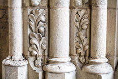 Antique building`s detail of white limestone pillars or columns. Antique church`s detail of white limestone pillars or columns with sculptured leaves Stock Image