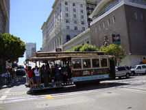 Antique Cable Car rides down  Powell Street with people hanging. SAN FRANCISCO - JULY 2: Antique Cable Car rides down  Powell Street with people hanging on side Royalty Free Stock Image