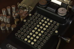 Antique calculator with coins stacks. Black antique calculator with mechanical push buttons and some coins stacks next to it Stock Image