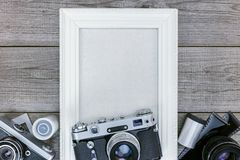 Antique cameras, negative films and white empty photo frame on w Stock Photo