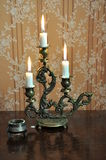Antique candelabra with three melting candles on an old wallpape Stock Photo