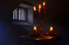 Antique candle burning in a dark room. Royalty Free Stock Image