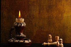 Antique Candle and Chess Pieces Royalty Free Stock Image
