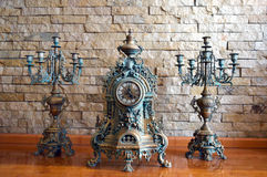 Antique candle holder and an old clock Royalty Free Stock Photography