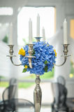 Antique candlestick with blue flowers wedding bouquet. Wedding candlestick with flower decoration before wedding ceremony. Table set for a wedding reception Royalty Free Stock Images