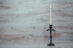 Antique candlestick with a burning candle Stock Images