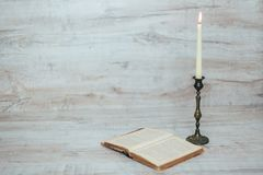Antique candlestick with a burning candle Stock Image