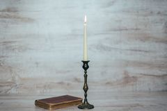 Antique candlestick with a burning candle Royalty Free Stock Photo