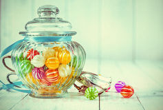 Antique candy jar filled with candies metal tongs. Low-angle view of an antique candy jar filled with colorful candies and ornate metal tongs on a wooden royalty free stock photo