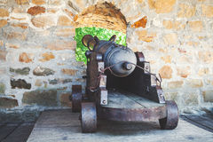 Antique cannon on gun carriage from loopholes fortress. Old cast-iron cannon on a wooden carriage at the loopholes of the fortress wall. Back view Stock Photos