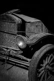 Antique car in black and white with front grill, tire, and headlamp visible. Stock Photo
