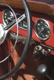 Antique car dashboard. A view of the steering wheel and dashboard or instrument panel of an old, antique car Stock Photo