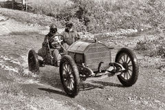 Antique Car Racing on Old Dirt Road. Antique 1912 Mercer Raceabout 35R speedster race car with traditional automobile driver and gentleman mechanic passenger in royalty free stock image