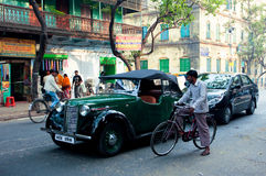 Antique car stoped on the road. Antique english car stoped on the road near the cyclist in Kolkata, India. Kolkata has a density of 814.80 vehicles per km road Stock Photo