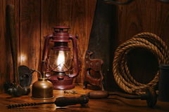 Antique Carpentry Wood Workshop  with Old Tools. Antique craftsman carpentry wood workshop with vintage kerosene lamp burning and old carpenter hand tools Royalty Free Stock Image