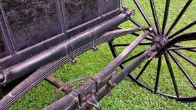 Antique  Carriage Wheel and  Axle Detail. Photo shows front part of an old  American black buggy or carriage wheel and frame sitting in grass in Pennsylvania Stock Image