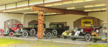 Antique Cars. Ketchikan, AK, USA - May 24, 2016: Anitque cars in various states of resroation displayed in a garage located in Totem Bight State Historic Site stock images