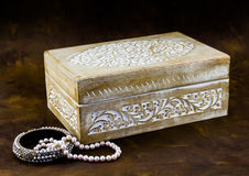 Antique carved pale wood box with peal jewellery on dark brown b Stock Photography