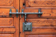 Antique carved wooden door with lock and handle. Part of old rustic door with metal lock and handle Stock Photos