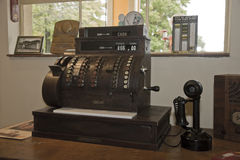 Antique Cash Register and Telephone. An antique cash register and telephone on a desk Royalty Free Stock Image