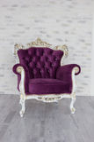 Antique chair from purple velvet in front of white room. Antique chair from purple velvet in front of white brick wall Stock Photography